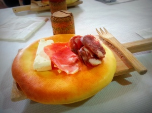 A rustic Shepherd's meal of pane (bread), creamy ricotta cheese, salty ham and some slices of a robust sausage